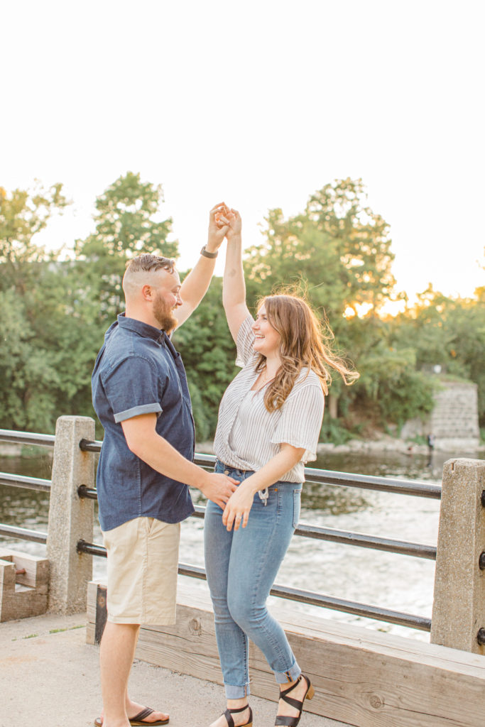 Dancing during engagement session - Watson's Mill Engagement Session Manotick - Bright & Airy photography - Grey Loft Studio - Ottawa Wedding Photographer - Ottawa Wedding Videographer - Engagement Session Locations in Ottawa - Summer Engagement session - Light blue and Cream with casual jeans and strap sandals. Ottawa Photo Studio.