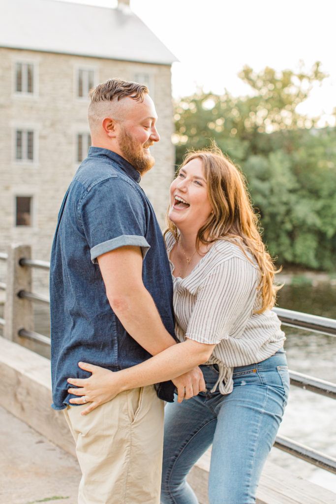 Couple having fun during engagement session - Watson's Mill Engagement Session Manotick - Bright & Airy photography - Grey Loft Studio - Ottawa Wedding Photographer - Ottawa Wedding Videographer - Engagement Session Locations in Ottawa - Summer Engagement session - Light blue and Cream with casual jeans and strap sandals. Ottawa Photo Studio.