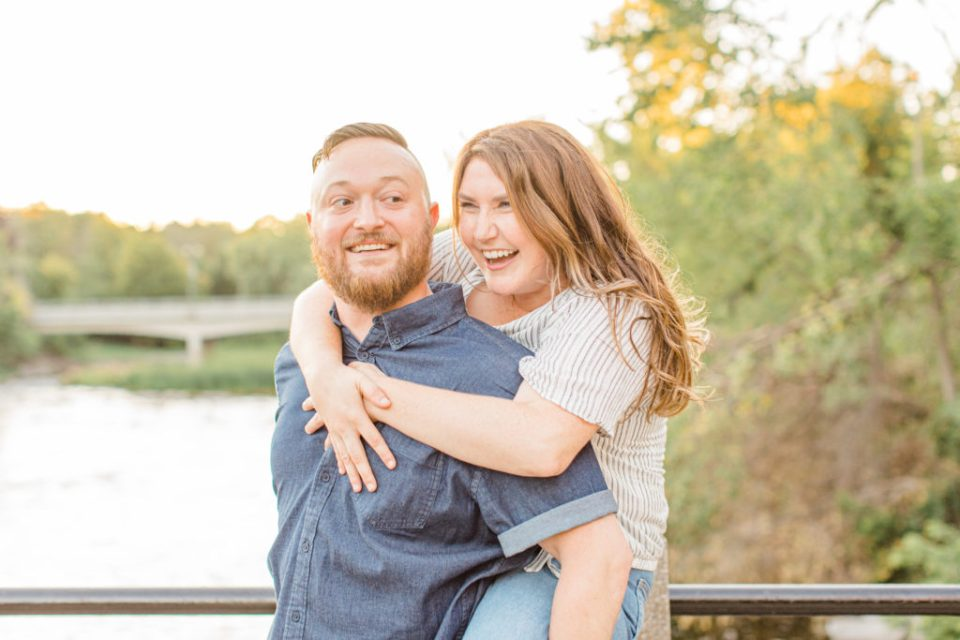 Couple having fun - Piggy Back Pose - Watson's Mill Engagement Session Manotick - Bright & Airy photography - Grey Loft Studio - Ottawa Wedding Photographer - Ottawa Wedding Videographer - Engagement Session Locations in Ottawa - Summer Engagement session - Light blue and Cream with casual jeans and strap sandals. Ottawa Photo Studio.