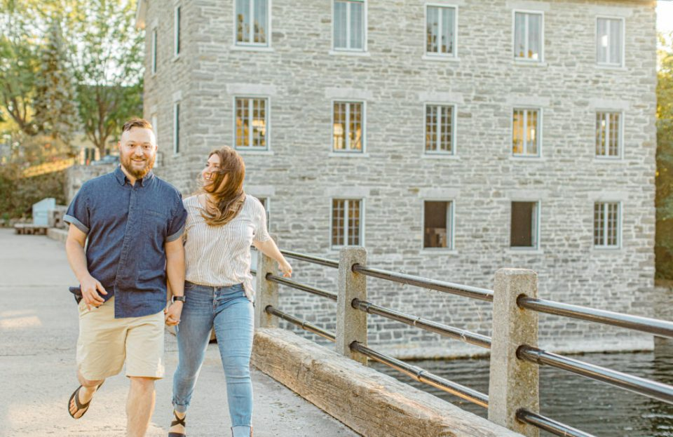 Couple holding each other close and walking-engagement session - Watson's Mill Engagement Session Manotick - Bright & Airy photography - Grey Loft Studio - Ottawa Wedding Photographer - Ottawa Wedding Videographer - Engagement Session Locations in Ottawa - Summer Engagement session - Light blue and Cream with casual jeans and strap sandals. Ottawa Photo Studio.