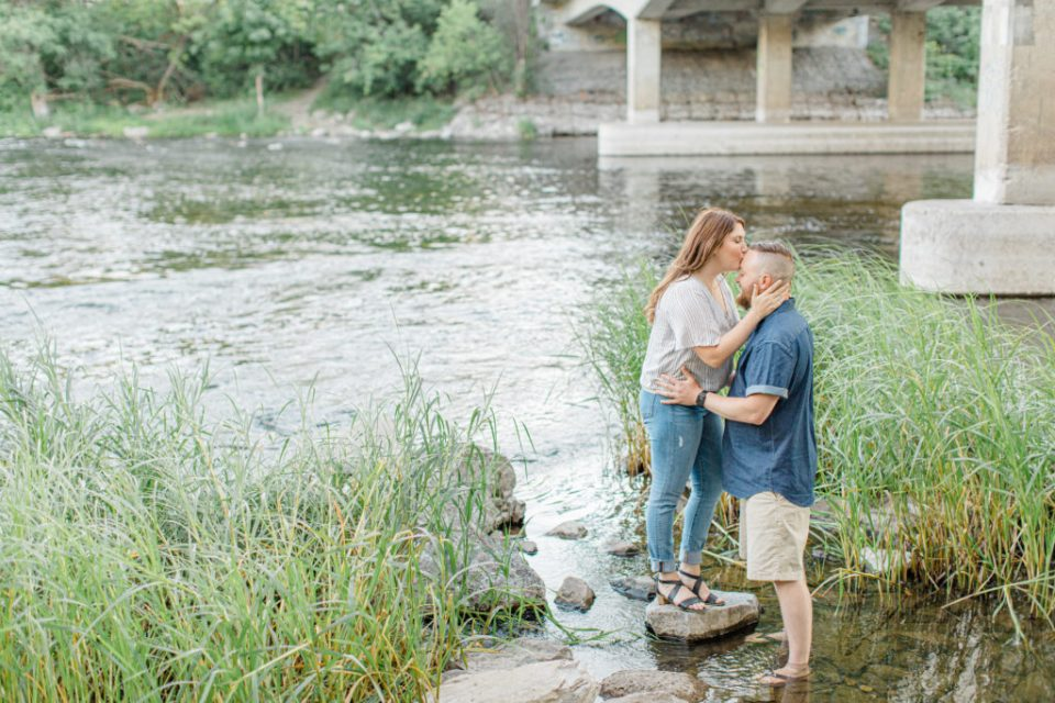 Couple kissing - kiss the forehead during engagement session - Watson's Mill Engagement Session Manotick - Bright & Airy photography - Grey Loft Studio - Ottawa Wedding Photographer - Ottawa Wedding Videographer - Engagement Session Locations in Ottawa - Summer Engagement session - Light blue and Cream with casual jeans and strap sandals. Ottawa Photo Studio.