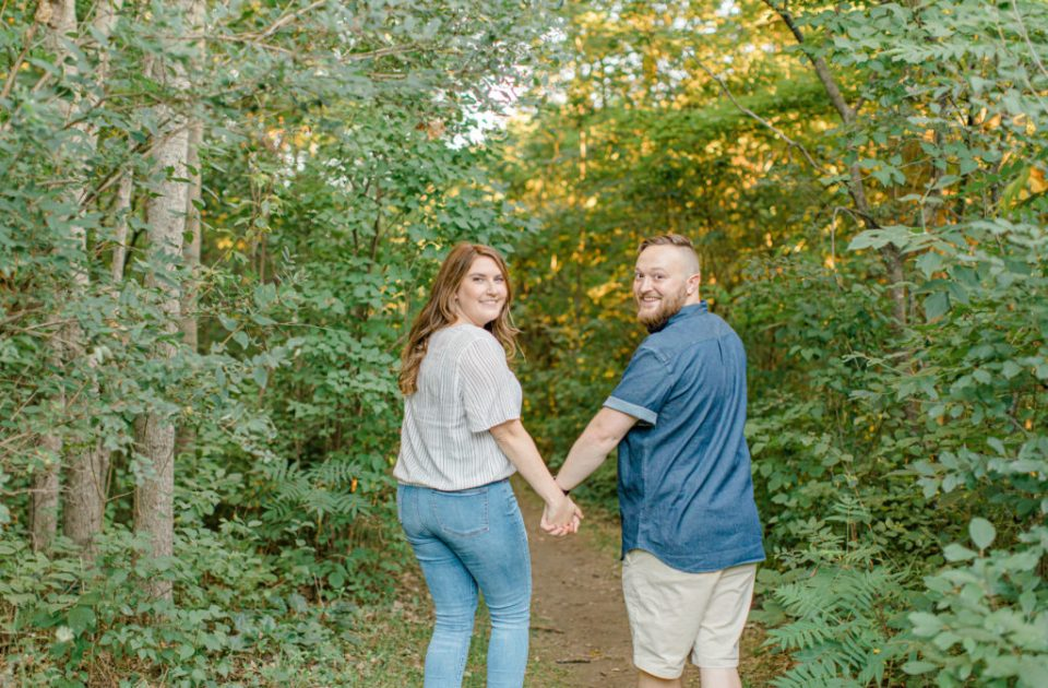 Hold hands look back at me! Watson's Mill Engagement Session Manotick - Bright & Airy photography - Grey Loft Studio - Ottawa Wedding Photographer - Ottawa Wedding Videographer - Engagement Session Locations in Ottawa - Summer Engagement session - Light blue and Cream with casual jeans and strap sandals. Ottawa Photo Studio.