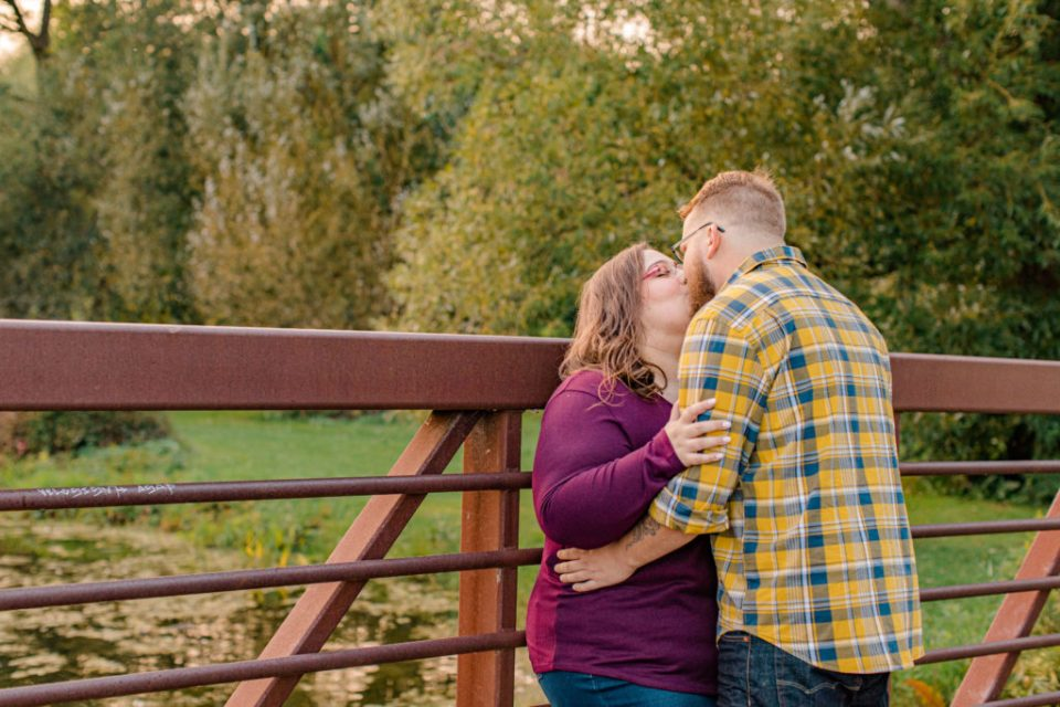 Kissing on the Bridge - Engagement Session - Ottawa Wedding Photographer - Grey Loft Studio - Wedding in Ottawa - Yellow & Plaid with Burgundy Knit Sweater and Jeans