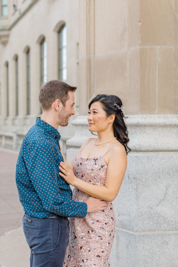 Couple during and Engagement Shoot Downtown Ottawa beside Chateau Laurier - Pink Floral Dress paired seamlessly with Blue Button Up Shirt and Dark Blue Khaki Pants.  Grey Loft Studio - Ottawa Wedding Photographer - Light and Airy photos, husband and wife Team.