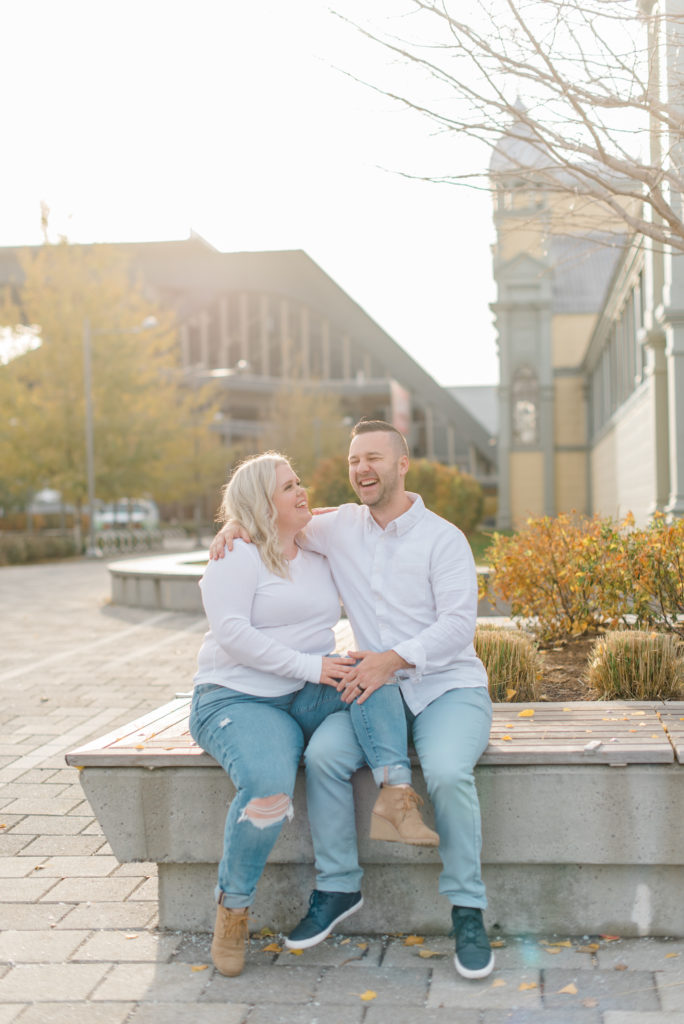 man and woman also husband and wife posing in downtown Ottawa at Lansdowne park wearing white shirts and blue jeans with the sun behind them on a warm November day - Posing ideas - Poses - Couple - Pose with Husband - Pose with Wife - Matching photoshoot - Matching couple