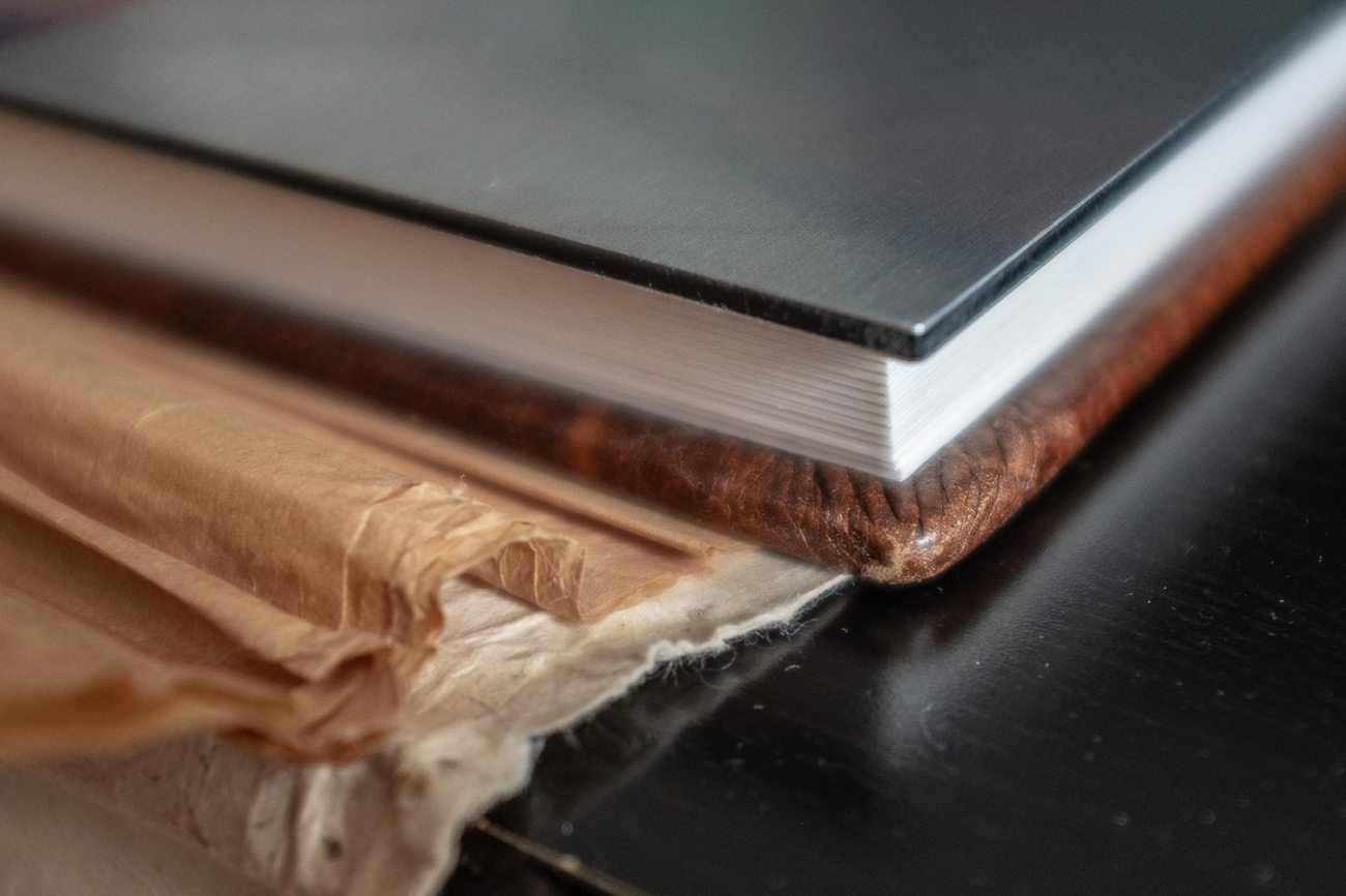 Custom wedding album with a metal cover and vintage brown leather binding. Minnesota Wedding Photographer