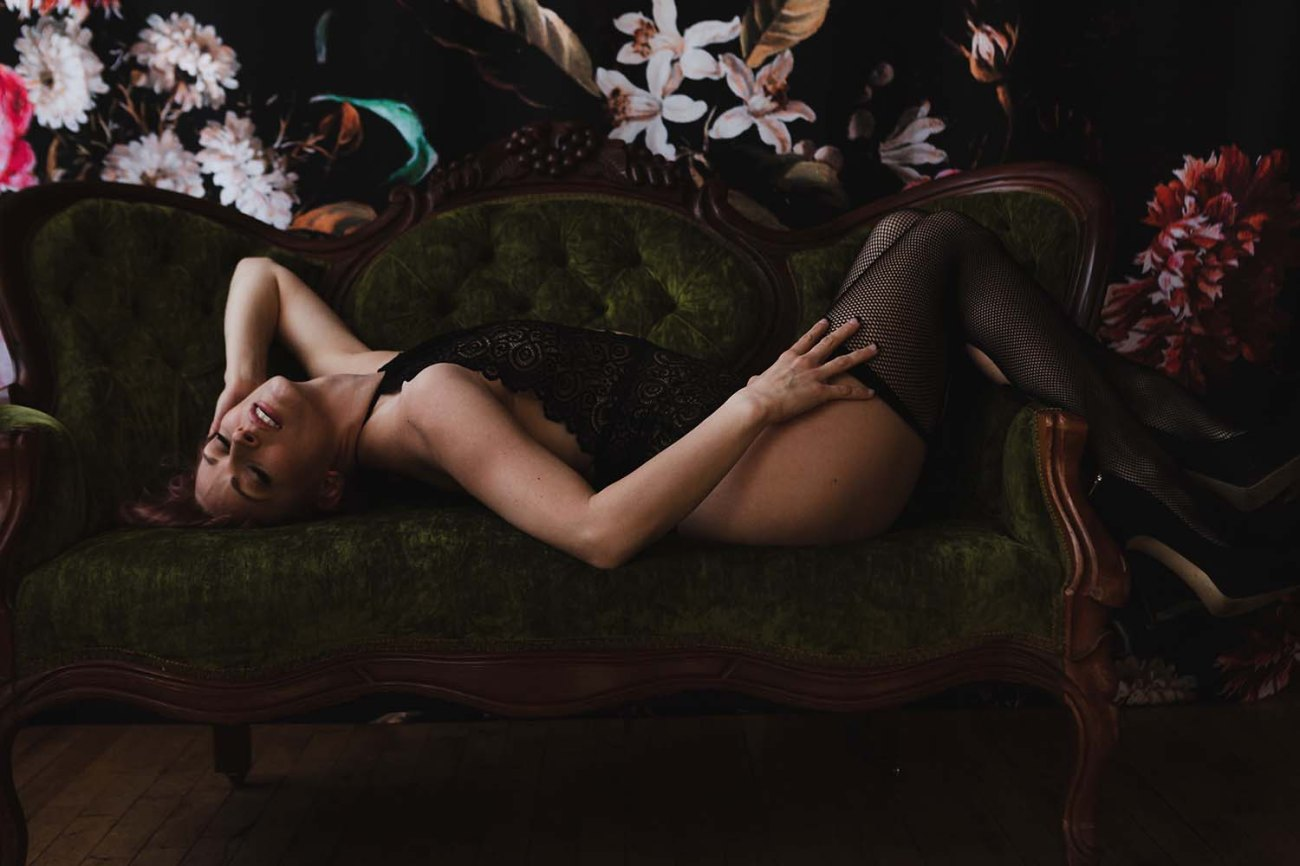 Curvy boudoir portrait with dark floral backdrop and the green classic couch. Twin Cities Boudoir Photographer