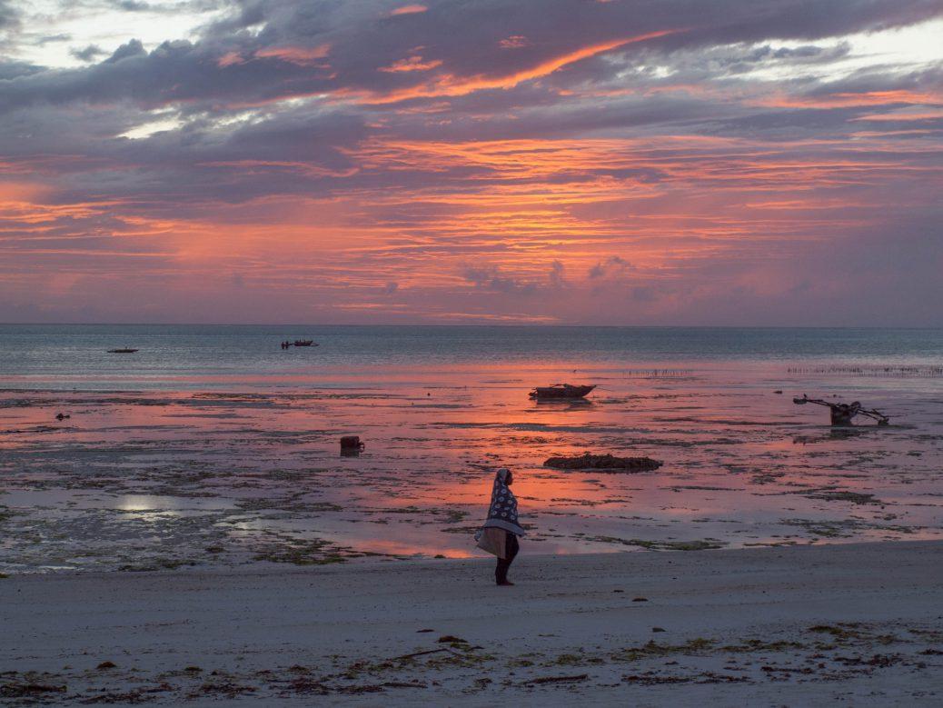 Sunset with woman at beach in Zanzibar
