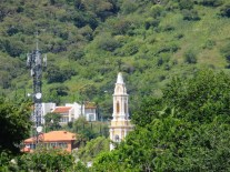 The spire of the San Juan Cosala church stands out against the lush green of the mountains.
