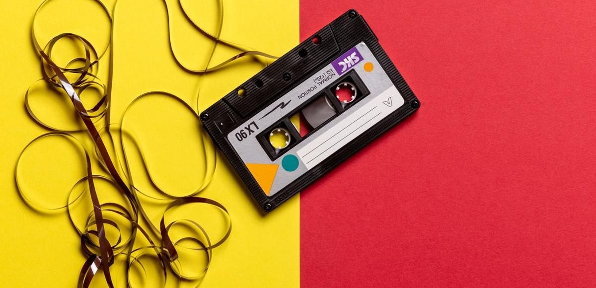 black cassette tape on top of red and yellow background