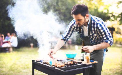 Mann am Grill macht gegrillter Kartoffelsalat