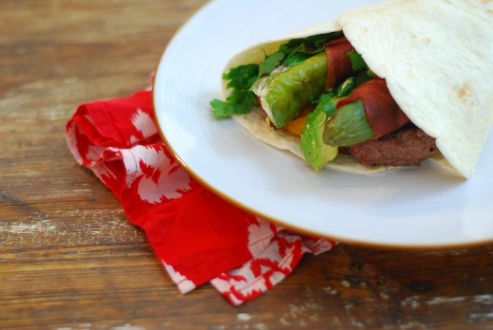 """A Mexican twist on the burger- a """"stuffed"""" burger with bacon wrapped cream cheese stuffed peppers, grilled tomatoes, avocado, cilatnro all wrapped in a flour tortilla."""