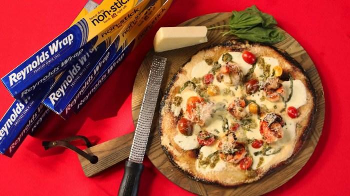 A shrimp, basil, cherry tomato, basil pesto and fresh mozzarella pizza