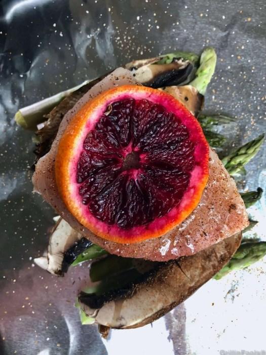 Blood orange topped swordfish with some asparagus and portobellos on the bottom