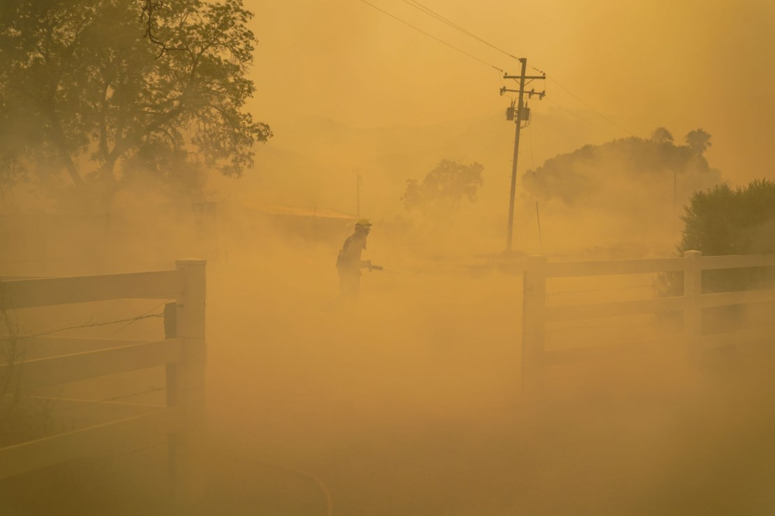 an orange smoky scene with trees, electrical wires and a lone firefighter
