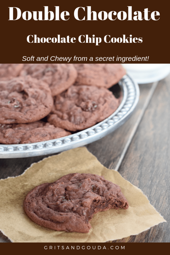 Double Chocolate Chip Cookies are soft and chewy from a secret ingredient. A bite is taken out of this one and placed on a piece of parchment. A glass of milk is close by to wash them down.