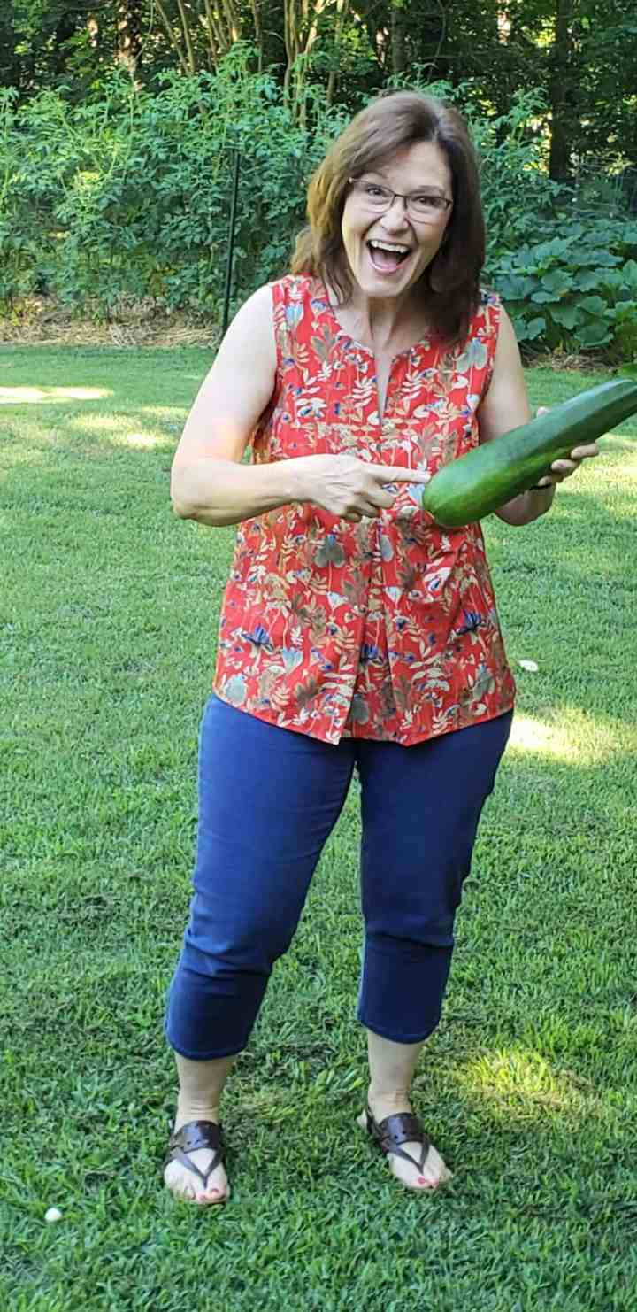 woman holding zucchini as big as a baseball bat