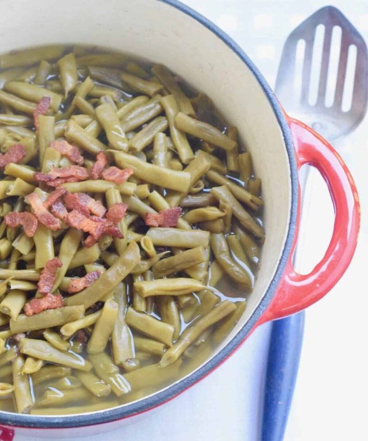 top view of red pot of green beans with crispy bacon on top; blue slotted spoon on surface