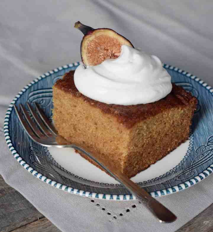 Fig Jam Cake with dollop whipped cream and fig half on a blue plate and fork
