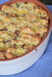 bacon sausage strata baked in stoneware dish on blue placemat