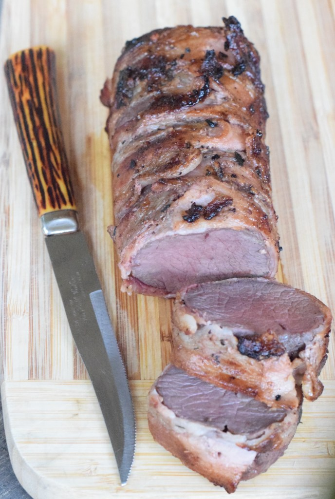 Baked sliced venison roast with slicing knife on a wooden cutting board