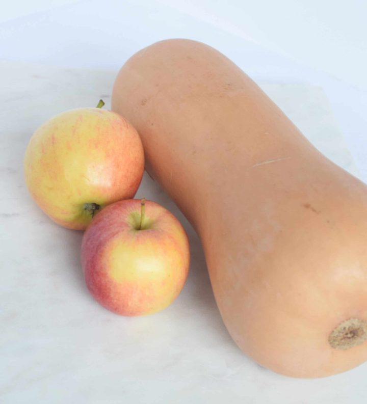 butternut squash on marble with two apples