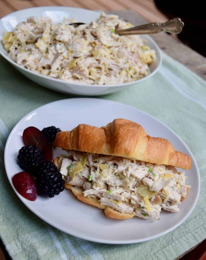 chicken salad in a croissant with blackberries and red grapes beside it