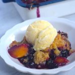 blueberry peach cobbler serving in white bowl wth whole cobbler in view