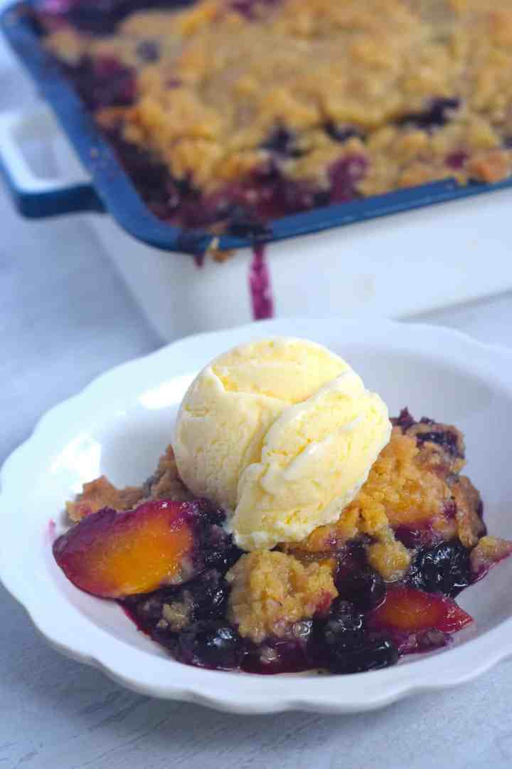 Blueberry Peach Cobbler in fluted serving bowl and whole cobbler in background