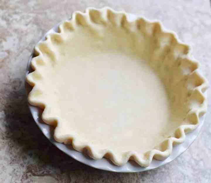 pie crust crimped in a white pie plate
