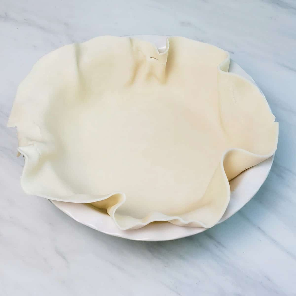Pillsbury pie crust unrolled and laid in a white pie dish on marble surface