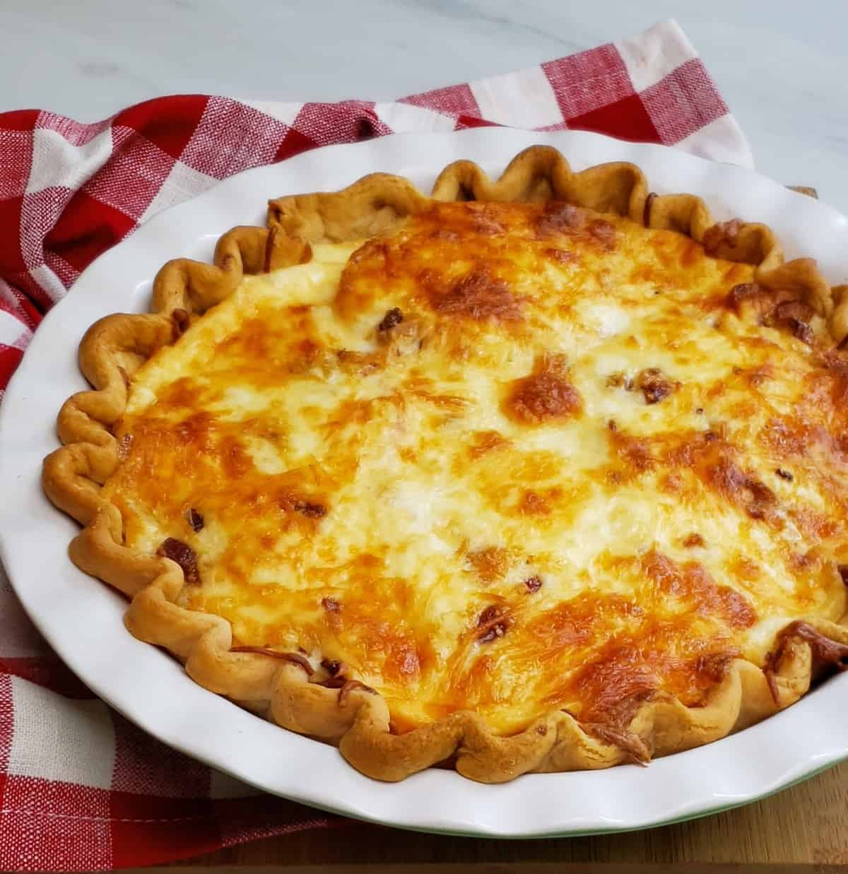 baked cheesy tomato pie, whole in white pie dish on a red checkered napkin