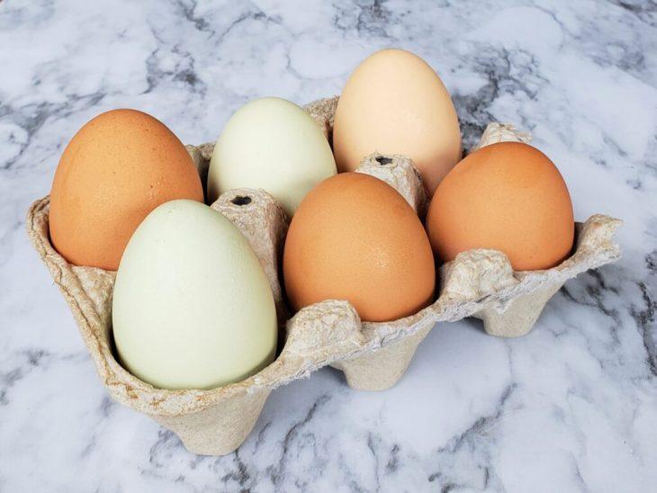 six farm eggs in a carton on marble surface