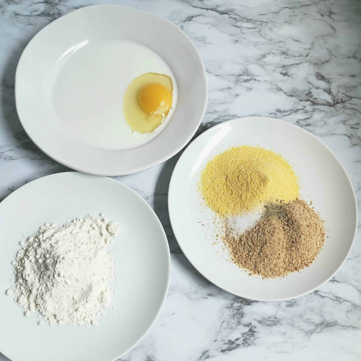 Three white plates with egg and milk mixture, flour, and cornmeal and breadcrumbs for dredging fried green tomatoes