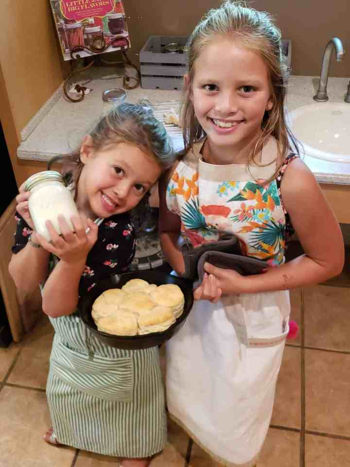 Two girls holding a cast iron skillet of biscuits and a jar of homemade butter