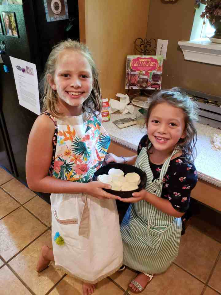 two girls holding unbaked biscuits in a cast iron skillet