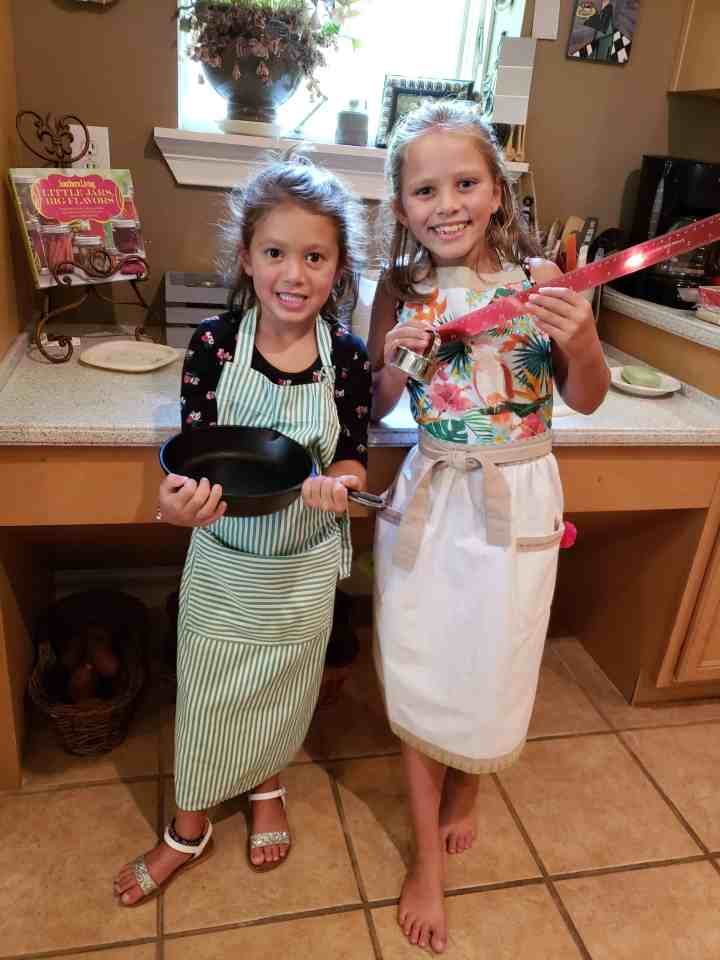 Two young girls holding a cast iron skillet and ruler and biscuit cutter wearing aprons