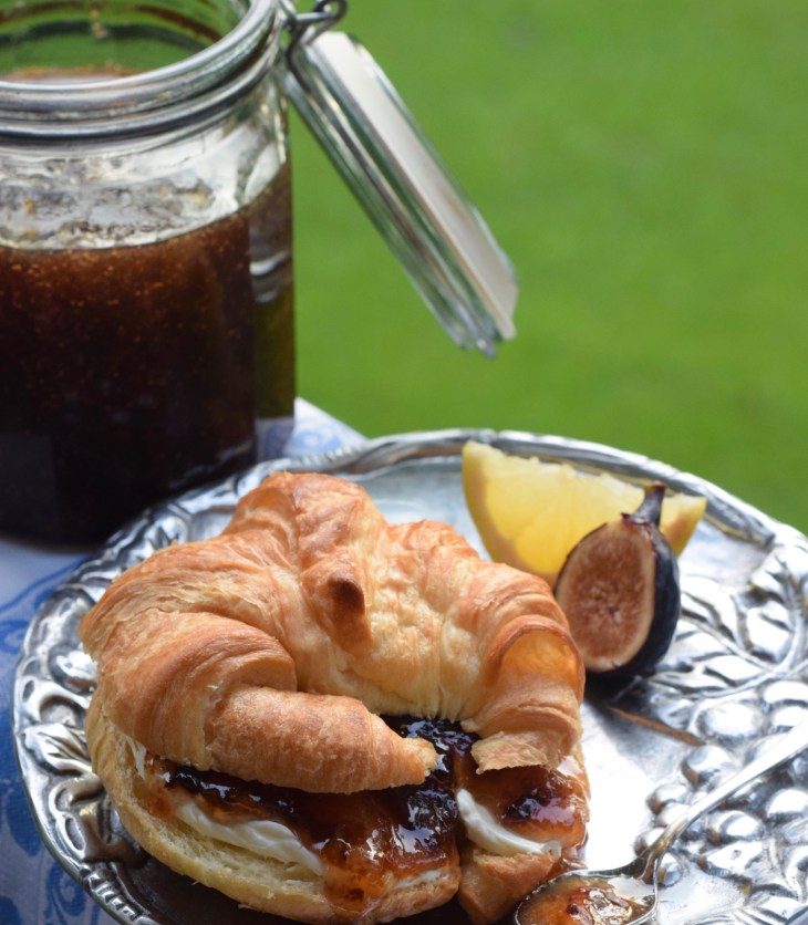 Fig and Lemon preserves on a bagel with cream cheese and jar of preserves in background