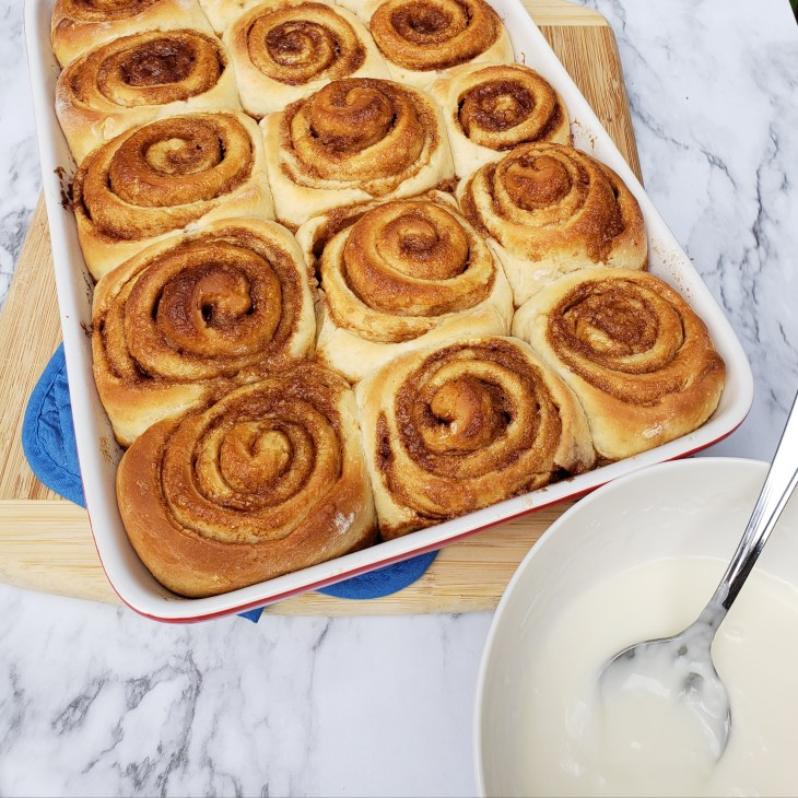 unbaked cinnamon rolls with bowl of icing