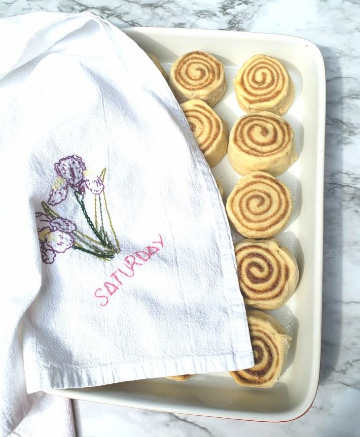 Unbaked cinnamon rolls with tea towel over half of them