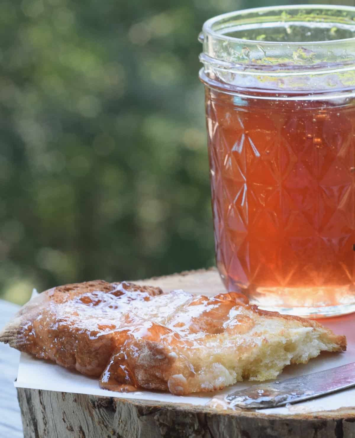 scuppernong jelly in jar with slice of crusty bread covered in jelly
