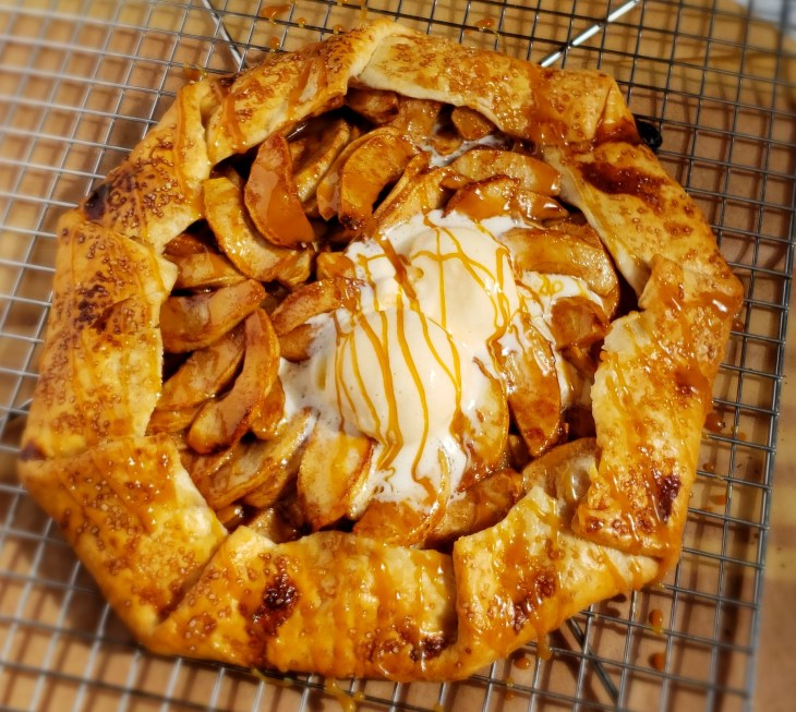 Apple pie galette with caramel drizzled and 2 scoops vanilla ice cream