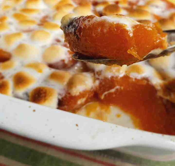 Spoonful of candied sweet potatoes lifted from white casserole dish