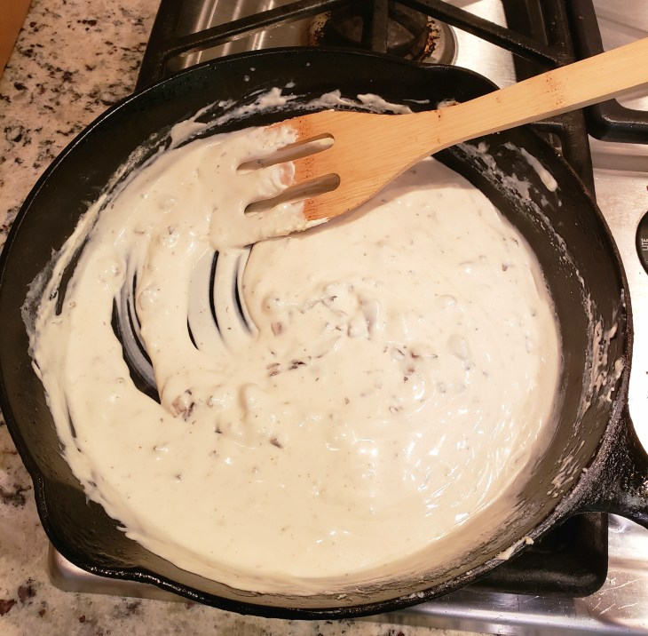 Cream cheese melting in chopped mushrooms in a cast iron skillet