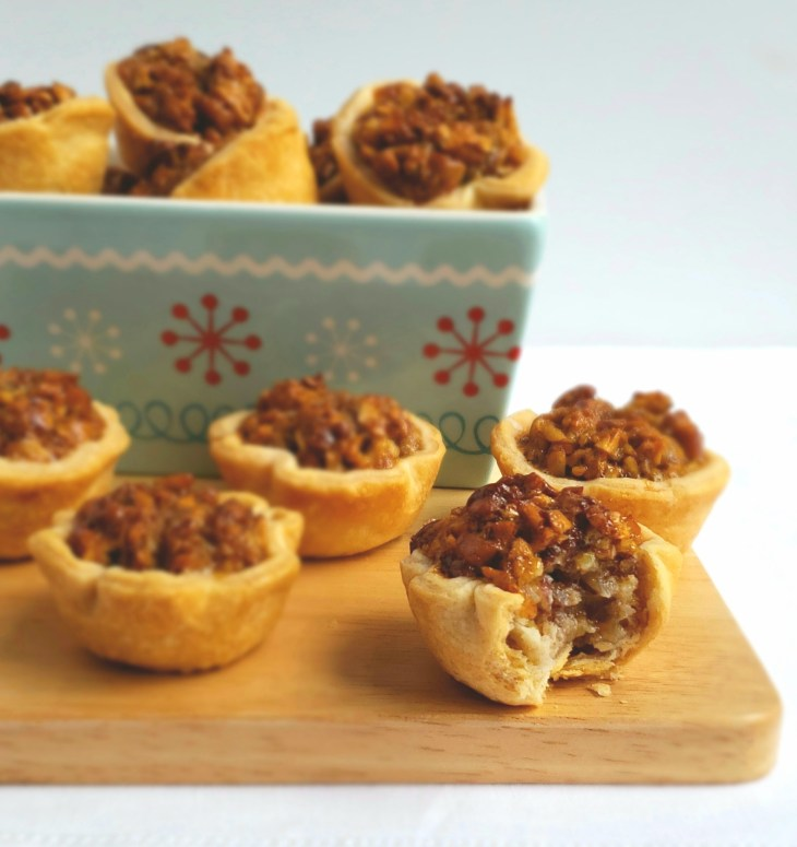 Maple Pecan Tassies are mini pecan pies. They are arranged on a wooden board and in a snowflake rectangle dish