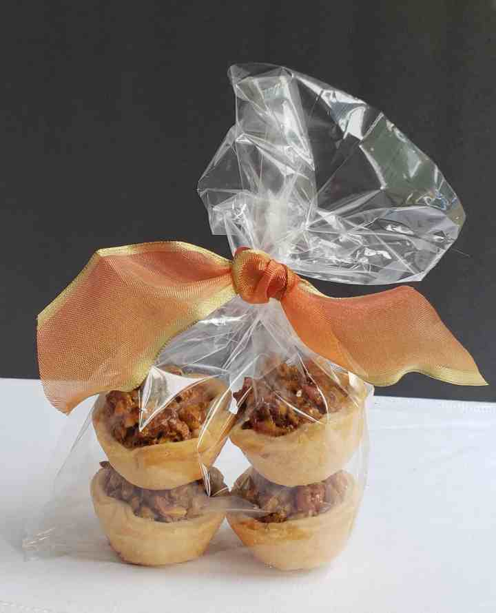 Four Maple Pecan Tassies wrapped in a clear bag with an orange bow