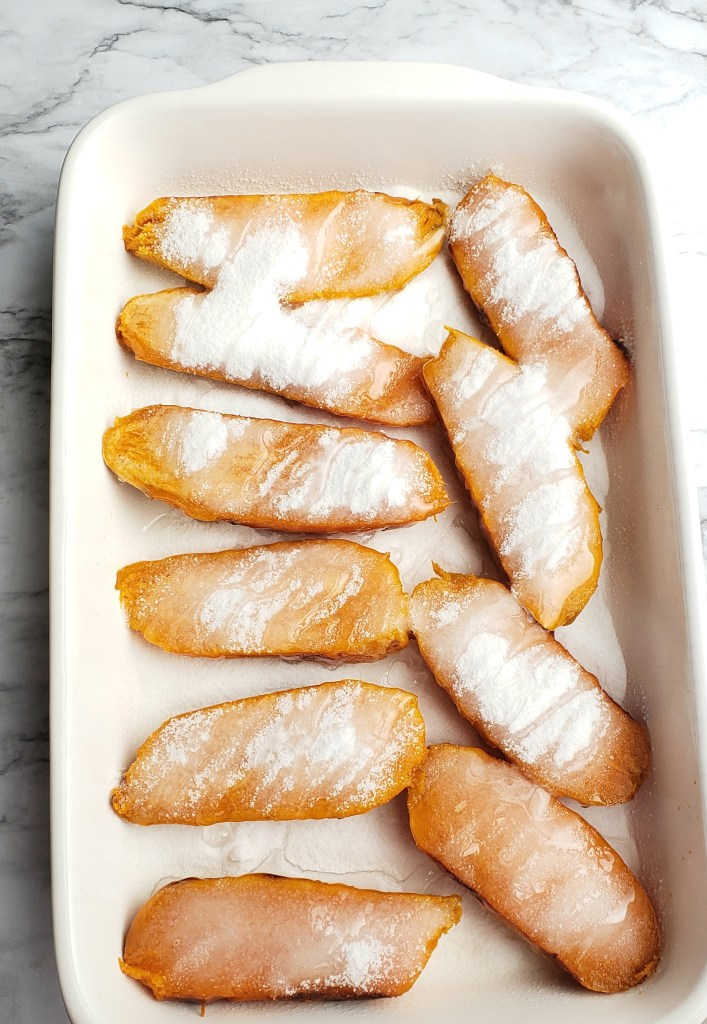 Sweet Potatoes halves are coated with sugar and drizzled with corn syrup and butter in a white casserole dish before baking