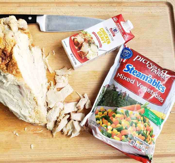 Turkey breast with some cut off the breast, a chefs knife on a cutting board, McCormicks chicken gravy and PictSweet mixed vegetables in package