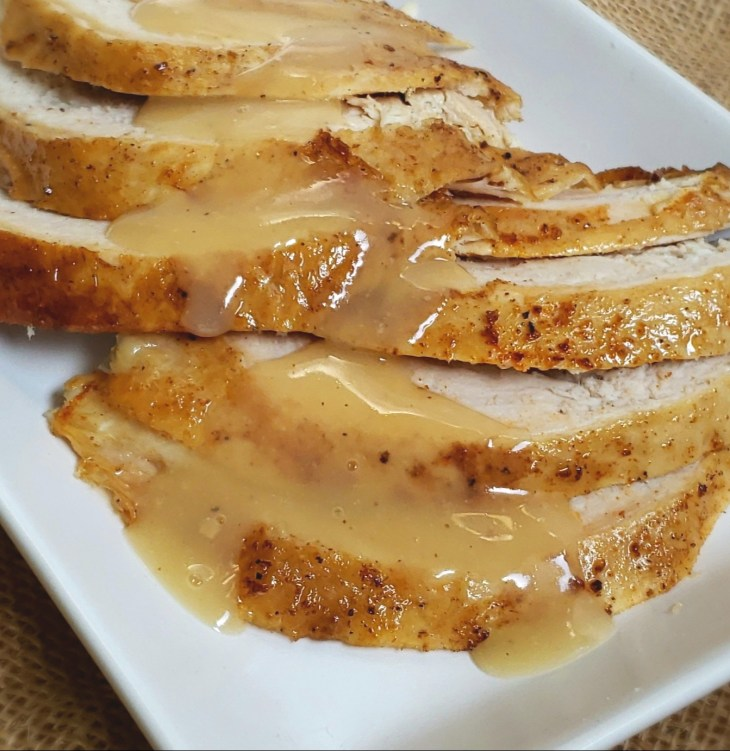 Slices of turkey breast on a white plate with gravy drizzled over the turkey