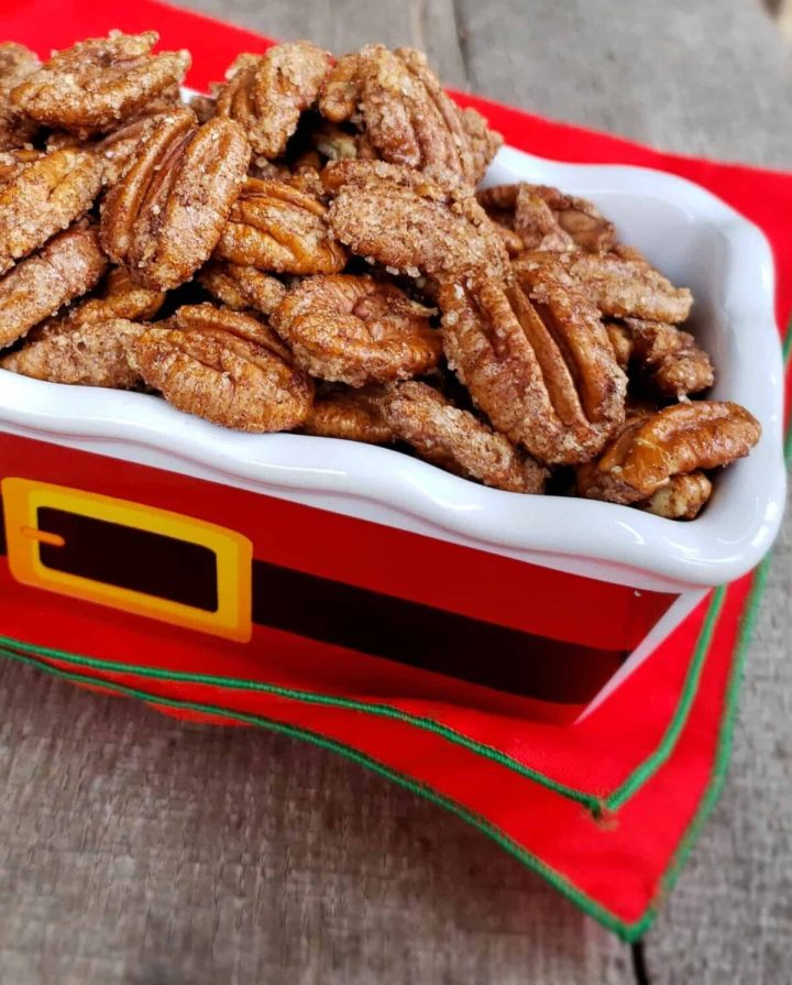3 Ingredient Cinnamon Sugar Pecans in a Santa belt motif rectangle dish on red napkin wtih green trim